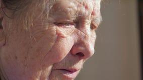 Plan rapproché du visage triste de la femme agée souffrant du tremblement secouant des paupières banque de vidéos