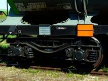 Plan rapproché en acier de roues de train avec les rails en acier envahis photographie stock