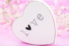 Plan rapproché en bois blanc de coeur avec amour de mot, sur le tissu de maille rose et les fleurs blanches Photo stock