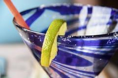 Plan rapproché extrême de lèvre de classe swirly bleue de margarita avec la chaux et le sel sur la jante - foyer sélectif photographie stock libre de droits
