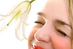 Plan rapproché femelle de sourire de visage avec le lis Images stock