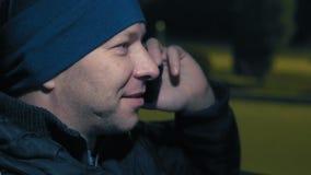 Plan rapproché, homme parlant au téléphone et séance de sourire à la roue d'une voiture la nuit dans le stationnement banque de vidéos