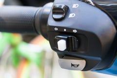 Plan rapproché l'éclairage de klaxon et de commutateur off/on de moto sur le guidon d'e-vélo photo libre de droits