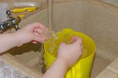 Plan rapproché, lavage petites tasses sous le jet d'eau, mains de bébé Image libre de droits