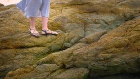 Plan rapproché les jambes des femmes dans les sandales et une longue jupe grise sont sur le bord de la mer rocheux à marée basse images stock