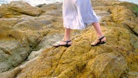 Plan rapproché les jambes des femmes dans les sandales et une longue jupe grise sont sur le bord de la mer rocheux à marée basse image libre de droits