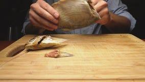 Plan rapproché Les mains masculines nettoient les poissons secs salés Sur la planche à découper mouvement 4k lent clips vidéos