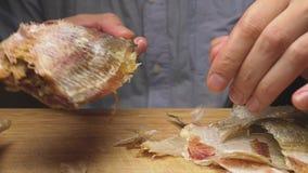 Plan rapproché Les mains masculines nettoient les poissons secs salés Sur la planche à découper mouvement 4k lent banque de vidéos