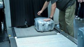 Plan rapproché les passagers prennent leurs sacs, bagages de bande de conveyeur, après qu'ils aient passé le scanner de bagage de banque de vidéos
