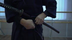 Plan rapproché, lien samouraï de mains à l'épée du ` s de katana de ceinture de kimono clips vidéos