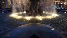 Plan rapproché lumineux de fontaine la nuit banque de vidéos