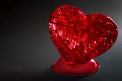 Plan rapproché lumineux rouge de coeur sur un fond gris-foncé Comme symbole du grand amour Images stock