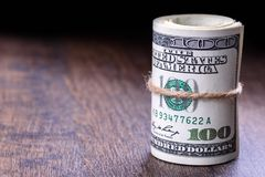 Plan rapproché, macro des billets de banque américains roulés du dollar du côté droit Fond en bois Photographie stock libre de droits