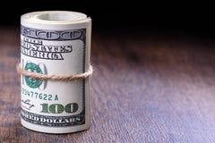 Plan rapproché, macro des billets de banque américains roulés du dollar du côté gauche Fond en bois Photos libres de droits