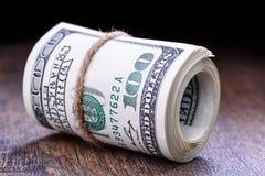 Plan rapproché, macro des billets de banque américains roulés du dollar Fond en bois Photo libre de droits