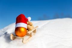 Plan rapproché peu de traîneau avec une boule de Noël dans la neige Images stock