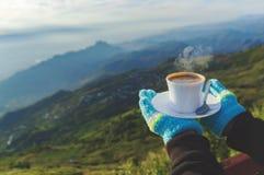 Plan rapproché qu'une tasse de café dans le voyageur remettent hors du Mountain View de foyer photographie stock