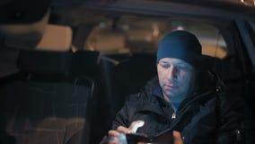 Plan rapproché, regards d'homme chez Smartphone se reposant à la roue de la voiture la nuit dans le stationnement banque de vidéos