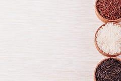 Plan rapproché rouge et noir et blanc de riz dans des cuvettes en bois sur le tissu beige photo libre de droits