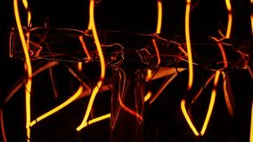 Plan rapproché rougeoyant classique de lampe d'edison sur le fond noir une vieille ampoule incandescente s'allume et sort en plan clips vidéos