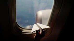 Plan rapproché Silhouette de la main d'un enfant avec le petit avion de papier dans la perspective de la fenêtre d'avion Séance d banque de vidéos