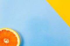 Plan rapproché simple de tranche de pamplemousse sur le dos bleu et diagonal de jaune images libres de droits