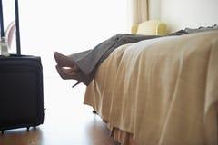 Plan rapproché sur des jambes de femme d'affaires s'étendant sur le lit Photographie stock libre de droits