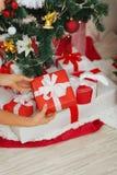 Plan rapproché sur des mains de femme mettant le cadeau de Noël Photos libres de droits