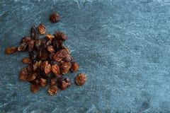 Plan rapproché sur des raisins secs sur le substrat en pierre Images stock