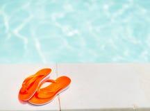 Plan rapproché sur des sandales s'étendant près de la piscine Images stock