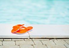 Plan rapproché sur des sandales s'étendant près de la piscine Photo libre de droits