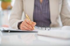 Plan rapproché sur l'écriture de femme d'affaires dans le document Photographie stock libre de droits
