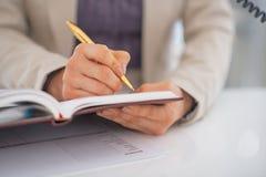 Plan rapproché sur l'écriture de femme d'affaires en journal intime Images stock