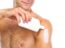 Plan rapproché sur l'homme appliquant la crème de bloc du soleil sur le bras Photographie stock libre de droits