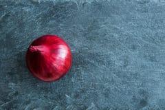 Plan rapproché sur l'oignon rouge sur le substrat en pierre Photographie stock libre de droits