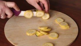 Plan rapproché sur la banane de coupe de femme sur la planche à découper banque de vidéos