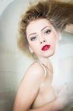 Plan rapproché sur la belle jeune femme attirante avec le rouge à lèvres rouge dans la baignoire se cachant derrière la main Photos libres de droits