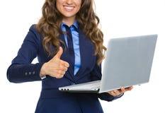 Plan rapproché sur la femme d'affaires avec l'ordinateur portable montrant des pouces  Images libres de droits