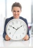 Plan rapproché sur la femme heureuse d'affaires avec l'horloge Photo libre de droits