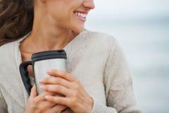 Plan rapproché sur la femme heureuse dans le chandail sur la plage avec la tasse de la boisson image stock