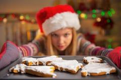 Plan rapproché sur la fille retirant la casserole des biscuits Photographie stock libre de droits