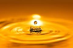 Plan rapproché sur la goutte de liquide cosmétique d'huile d'or photo stock