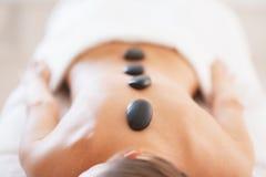 Plan rapproché sur la jeune femme décontractée recevant le massage en pierre chaud Photos stock