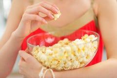 Plan rapproché sur la jeune femme mangeant du maïs éclaté Photo stock