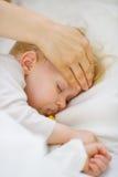 Plan rapproché sur la mère contrôlant la température de la chéri Photographie stock libre de droits