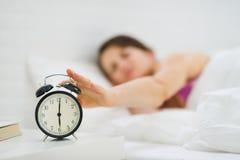 Plan rapproché sur la main de femme atteignant pour arrêter l'horloge Image stock