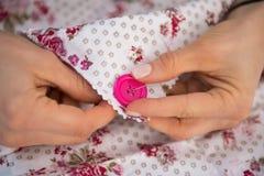 Plan rapproché sur le bouton de couture d'ouvrière couturière Photo stock