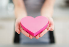 Plan rapproché sur le coeur à disposition de la jeune femme Images stock
