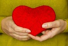 Plan rapproché sur le coeur rouge fait à partir de la laine disponible de la femme Photos stock