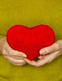 Plan rapproché sur le coeur rouge fait à partir de la laine disponible de la femme Photo libre de droits